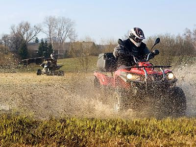 A man driving a quad bike through a muddy filed, with someone else on a quad bike in the background