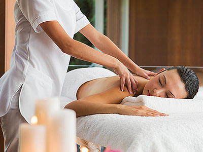 A woman receieving a back massage on a table from a beauty therapist