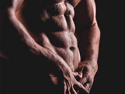 A naked man's torso with a six-pack to a black backdrop