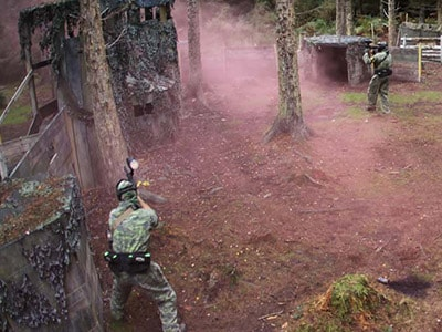 Some men in a forest with pink smoke coming from a paint grenade