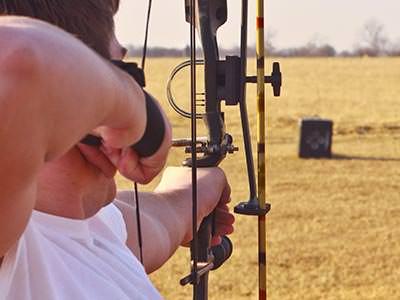 A man firing an arrow at a target in the distance