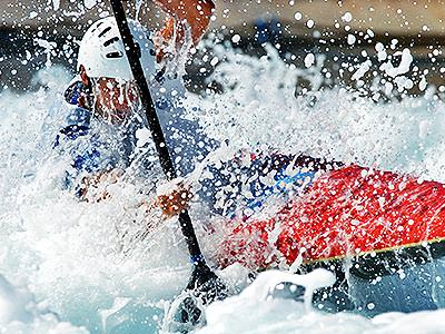 A man kayaking on a furious river with water splashing up him