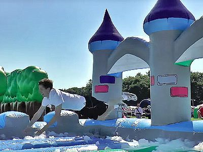 A man jumping through an inflatable castle onto foam
