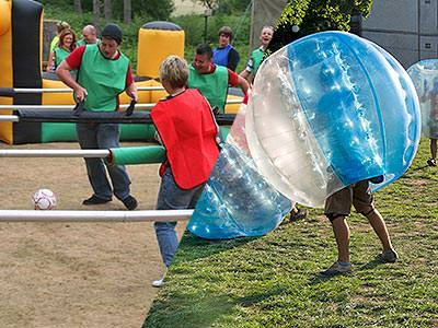 A split image of people playing human table football and bubble football