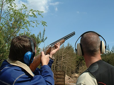 A man being taught to fire a gun at a clay pigeon
