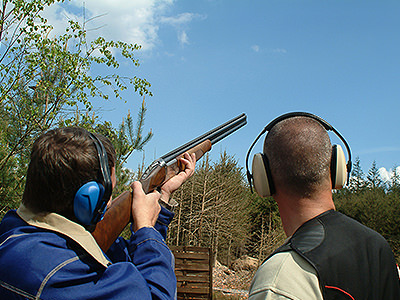 Two men with ear protectors on, one aiming his gun into the sky
