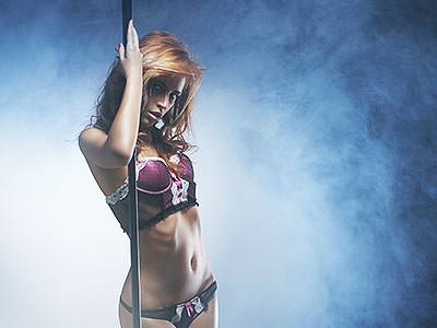 A woman in her underwear holding a pole and looking into the camera seductively