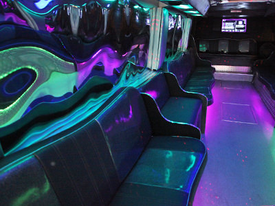 The interior seating in the private party bus to a backdrop of lights