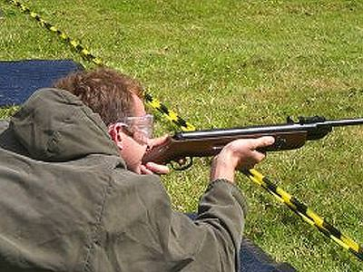 A man lying on the ground outdoors and aiming with an air rifle