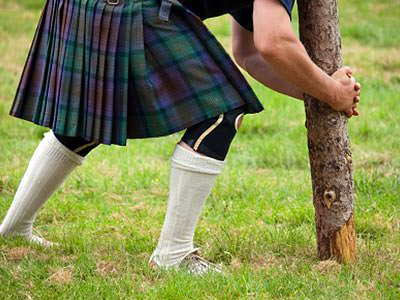 Close up of a man in a kilt, attempting to pick up a log