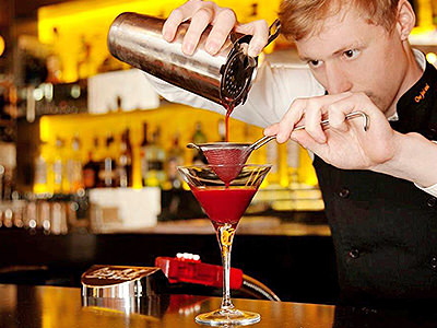 A man pouring a red cocktail through a sieve, into a glass