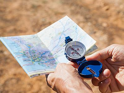 A hand holding a map and a compass
