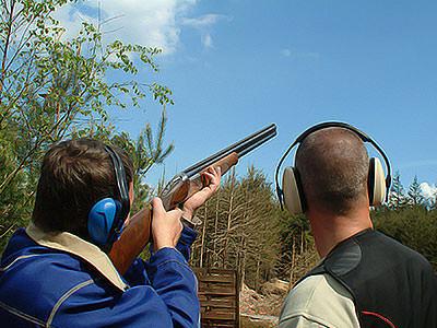 A man aiming a shotgun into the sky next to a man looking away