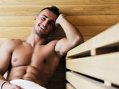 A man looking into the camera, whilst in a sauna