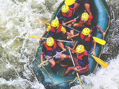 A bird's eye view of some people on a raft battling white water rapids