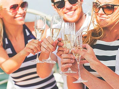A group of smiling people clink their glasses of champagne together