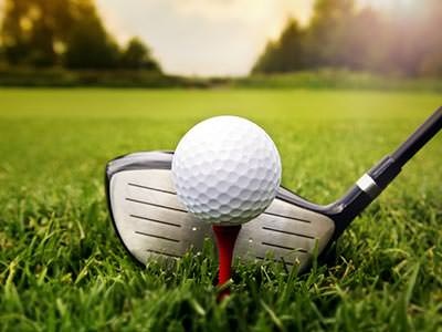 A golf club addressing a ball on a tee