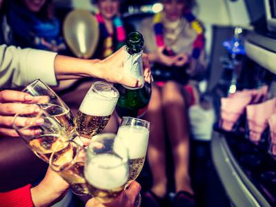 A cluster of champagne glasses being filled inside a large vehicle