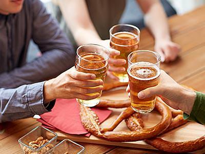 Three men raise glasses of beer together over a platter of pretzels