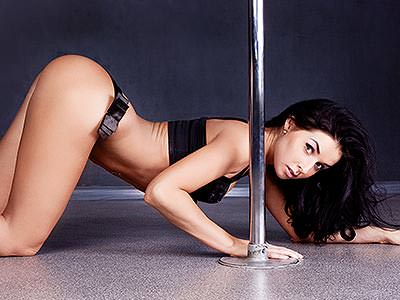 A woman in black underwear posing on all fours behind a pole dancing pole