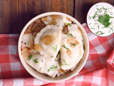 A bowl of traditional Polish dumplings next to a bowl of white sauce