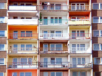 A multicoloured block of old-fashioned flats with balconies