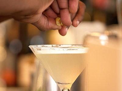 A man squeezing lemon above a cocktail