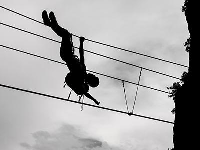 A person hanging upside down from a set of cables, silhouetted against a grey sky