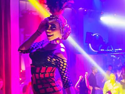 A woman in a cabaret outfit posing in front of a busy club