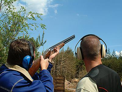 A man aiming a shotgun into the sky next to a man looking away
