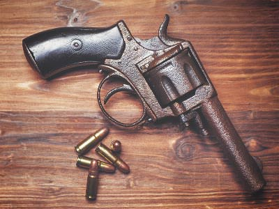 An old-fashioned revolver handgun lying on a wooden surface, next to some ammunition