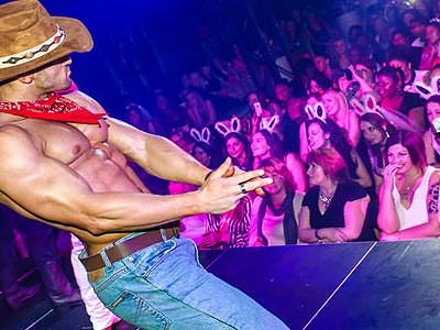 A man in a cowboy hat and jeans on stage and performing for The Dreamboys to a crowd of women