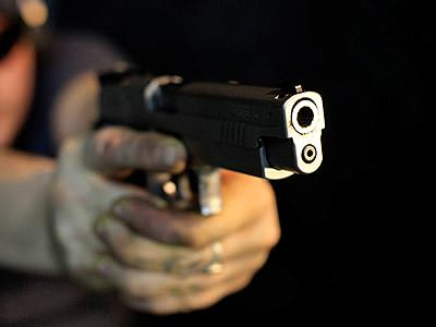 A pair of hands aiming a handgun past the camera