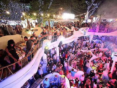 People dance and drink in a large, multi-level, open air venue