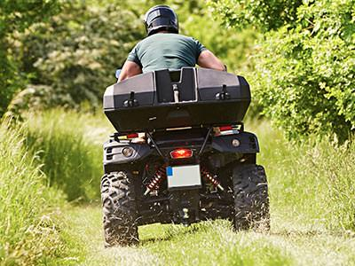 The back of a man driving a quad bike outdoors in a field