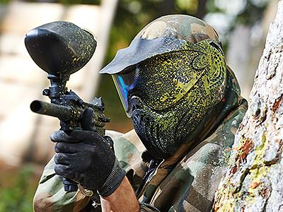 A man wearing a paintball mask covered in yellow paint aims a paintball gun from behind a tree