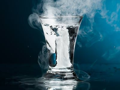 A glass filled with clear, smoking liquid