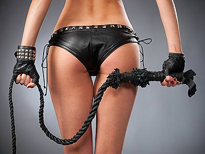 A woman's bum, wearing leather underwear and gloves and holding a rope whip