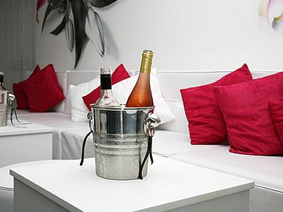 A silver wine cooler containing two bottles of wine on a white table, next to a white sofa with red and white cushions