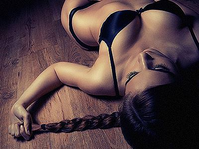 A woman lying on the ground in her underwear, pulling on her hair