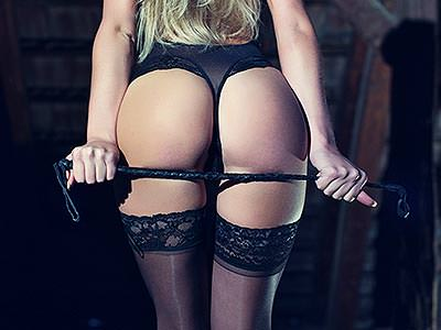 A woman's bum, wearing a thong and suspenders and holding a whip against the back of her legs