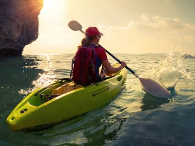 A woman heading out to sea on a kayak at sunrise