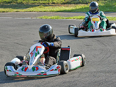 Two go karts racing on an outdoor circuit