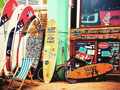 Some surfboards lined up outside a surf shop