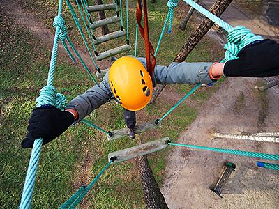 Top-down view of a person in a yellow helmet on a high ropes course