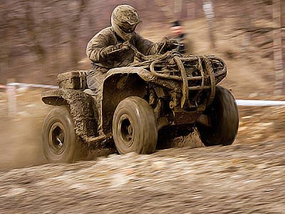 A mud-covered man driving a mud-covered quad bike