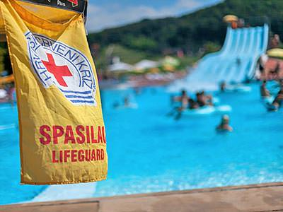 A yellow lifeguard flag in the foreground with a slide and swimming pool in the background
