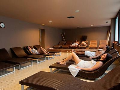 A group of men and women wearing towels reclining on brown loungers in a light room
