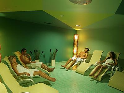 A group of men and women wearing towels recline in loungers in a green room