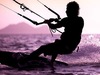 A man holding onto a harness and wakeboarding
